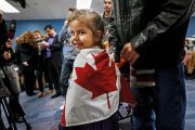 Syrian child wrapped in Canadian flag