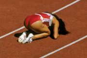 Competitive sprinter kneeling on race track