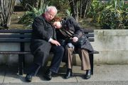 Couple sleeping on bench in London