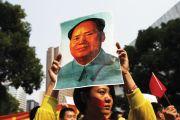 Demonstrator holding poster of Mao Zedong (Mao Tse-tung), Shanghai