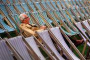 Elderly man sitting alone in rows of deckchairs