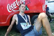 Exhausted marathon runner sitting by Coca-Cola branded vehicle