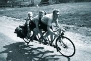 Family riding three-seat bicycle