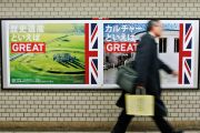 Pedestrian walks past 'GREAT' campaign posters