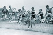 People jumping over tennis net