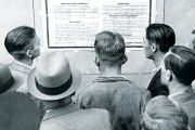 Group of men reading from notice board