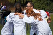 people wearing lab coats huddling together