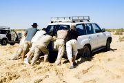People pushing car stuck in sand