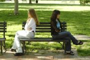 Two people facing away from each other on a bench