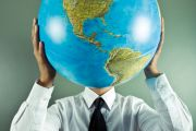 Man holding globe in front of face