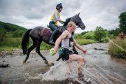 Man racing horse across shallow river