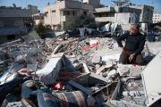 Man sits in rubble of Palestinian National Authority Council of Ministers building