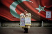 Man standing in front of Turkish national flag