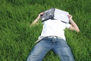 A man lying in the grass covering his face with a laptop
