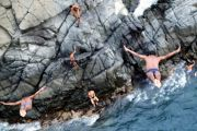 Men diving off cliff into sea