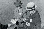 Men paying out winnings at a racecourse