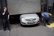 Men looking at car stuck under garage door