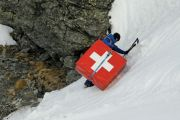 Mountain climber carrying safety mattress bearing Swiss flag