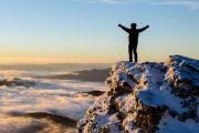 Person celebrating reaching top of mountain