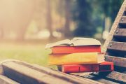 Pile of books on park bench