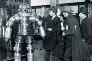 Men examining 1950s-style robot