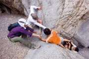 Rock climbers helping man overcome obstacle