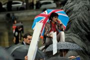 Sad woman with Union flag umbrella in rain at Trafalgar Square