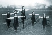 schoolgirls balancing a ball and plate on their heads while spinning a hoop