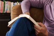 Seated man on sofa reading book