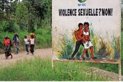 Congolese women walk past a sign opposing sexual violence