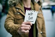 "Woman holding a ""me too"" sticker"
