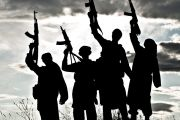 Silhouettes of Islamic terrorists aiming guns at sky