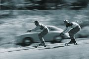 Skiers racing car down hill