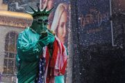 A man dressed up as the Statue of Liberty holding a mobile