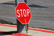 Stop sign rested against street sign pole