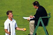 tennis player talks to umpire