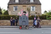 people dressed in medieval costume towing a homemade castle