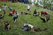 Competitors tumble down Coopers Hill in pursuit of a round Double Gloucester cheese during an annual cheese rolling competition