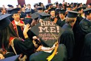 Graduating student displays a Hire me sign written on his mortar board