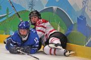 two female ice hockey players lying on the ice