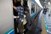 People cram on to a train in Japan