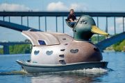 man driving giant duck on river