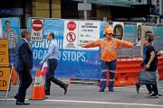 A worker directs pedestrians on a street in the central business district of Sydney