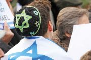 A Israeli youth with a flag draped around his back. Star of David, Jewish.