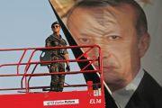 Turkish police officer standing in front of poster of President Recep Tayyip Erdoğan