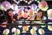 Two women look at pollen robots in Japan