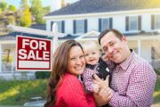 Young couple with baby next to house for sale sign