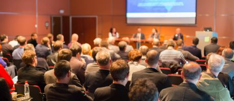 Conference audience illustrating return to in-person events via  hybrid mode