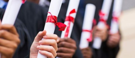 Group of graduates holding degree certificates