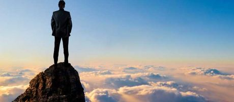 Man on top of mountain above clouds
